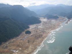 Indonéské pobřeží v oblasti Aceh na Sumatře, zasažené tsunami v prosinci 2004. Ani tato novodobá katastrofa se zdaleka neblížila projevům impaktní tsunami, která zdevastovala pobřeží Severní Ameriky až do hloubky desítek kilometrů. Kredit: AusAID, Wikipedie (CC BY 2.0)