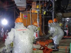 Skupina pracující na zasunutí trubky do potrubí přímo u vybudovaného přístupu k potrubí (zdroj TEPCO).