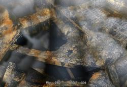 Obrázek z průzkumu v nitru kontejnmentu druhého bloku. Je vidět díra, ve které chybí roštová podlaha. Bílé závoje vznikají vlivem radiace. (Zdroj TEPCO).