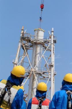 Instalace víka na společný ventilační komín prvního a druhého bloku po jeho zkrácení o polovinu (zdroj TEPCO).