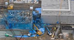 """Likvidace """"Místnosti Atomového muže"""", jejíž budova propojuje hlavní budovu produkci plutonia s budovou se zařízením pro jeho recyklaci. Modrý sprej slouží k fixaci prachu a tím i případných radioaktivních částic. (Zdroj David Wyatt DOE)"""