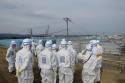 Pracovníci Mezinárodní atomové agentury před nádržemi na kontaminovanou vodu (zdroj TEPCO)