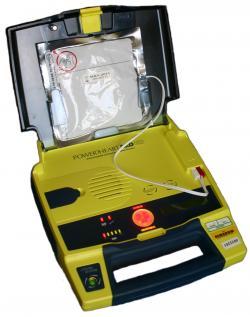 Automatický defibrilátor, určený pre použitie laikom. Samolepiace elektródy sú pripravené vo veku prístroja. Defibrilátor vie rozprávať - diktuje záchrancovi, čo má urobiť, netreba sa zdržovať čítaním nejakého návodu. Potrebu elektrického výboja vyhodnotí sám prístroj a po upozornení ho aj spustí. Pacienta sa vtedy nemá nikto dotýkať, mohol by dostať podobnú nepríjemnú ranu, ako od vadného elektrospotrebiča (ale nebude ohrozený).  (Kredit: Owain Davies , Wikipedia , CC BY 3.0)