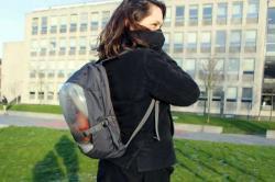 Dívka s batohem plným živých rostlin a k němu připojenou dýchací maskou. Foto z Delft zde dne 18. ledna 2016. (Kredit: Marnix de Kroon, TU Delft)
