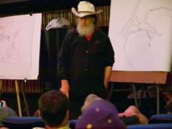 Autor knihy Robert T. Bakker při jedné ze svých přednášek v roce 2011. Bakker dlouhodobě využívá své výborné ilustrátorské schopnosti, aby podpořil své často poněkud neobvyklé názory. Mezi ty patří například i představa živorodých sauropodů. Kredit: etee, Wikipedie (CC BY-SA 2.0)