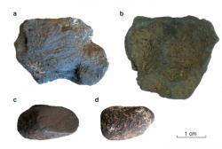 Dva z burelových artefaktů nesou zřetelné stopy používání. Na tom vlevo nahoře jsou vidět vrypy po škrábání ostrým tvrdým nástrojem. Vlevo dole rovná ploška svědčí o broušení. Oběma způsoby se z minerálu dal získat prášek MnO2. Foto: Peter Heyes. Obrázek ve velkém rozlišení zde.