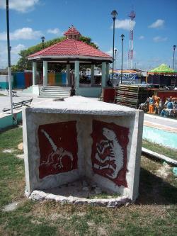 """Stéla představující """"pomník dinosaurů"""", umístěná příhodně v městečku Puerto Chicxulub. Před 66 miliony let se právě na tomto místě odehrála jedna z nejkatastrofičtějších událostí v dějinách vyspělého rozvinutého života na Zemi. Kredit: Adamcastforth, Wikipedie (CC BY-SA 3.0)"""