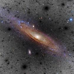 Umělecká vize chuchvalců temné hmoty kolem Mléčné dráhy. Kredit: V. Belokurov, D. Erkal, S.E. Koposov (IoA, Cambridge). Photo: Color image of M31 from Adam Evans. Dark matter clumps from Aquarius, Volker Springel (HITS).