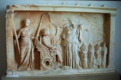 Triptolemos na dračím voze, asi se vypravuje distribuovat po světě setbu obilí, kterou dostal od bohyně. Archeologické muzeum v Eleusině. Kredit: Zde, Wikimedia Commons.