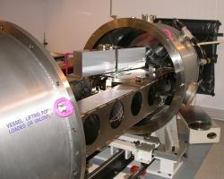 Spektrograf HARPS. Na snímku je otevřená vakuová nádrž, a tak lze vidět některé z vnitřních součástí. Například k lavici připevněná optická mřížka rozptylující přicházející světlo  o rozměrech  200 x 800 mm. Kredit: ESO.