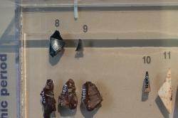 Vlevo nahoře jsou hroty z obsidiánu nalezené v jeskyni Franchthi, pod nimi pazourky. Obsidián přivezli z kykladského ostrova Mélu. Závěr paleolitu, 10 až 8 tisíc let před n. l. Archeologické muzeum v Naupliu. Kredit: Zde, Wikimedia Commons. Licence CC 4.0.