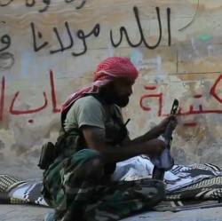Syrsk� rebel b�hem bitvy o Aleppo (2012). Kredit: VOA News; Scott Bobb / Wikimedia Commons.