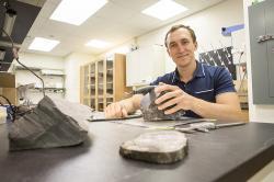 Paleontolog Erik Gulbranson z University Wisconsin v Milwaukee s fosilizovanými stromy, které si přivezl z Antarktidy. Jsou z doby kdy se ještě na Zemi  nestihli vyvinout dinosauři. Kredit: UWM Photco / Troye Fox             Read more at:https://phys.org/news/2017-11-geologists-uncover-antarctica-fossil-forests.html#jCp