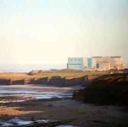 Pobřeží u Hinkley Point, Somerset, snezbytnou jadernou elektrárnou. Kredit: Richard Baker / Wikimedia Commons.