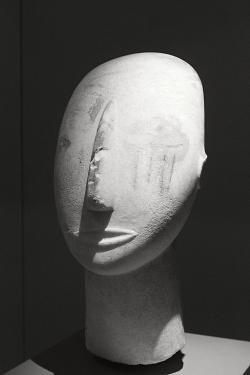 Hlava bohyně z Amorgu se zbytky polychromie, mramor je z ostrova Paru, 2800-2300 před n. l. Oči jsou zobrazeny malbou. Ve tváři jsou namalované čtyři svislé pruhy, původně prý byly červené. Národní archeologické muzeum v Athénách, č. 3909. Kredit: Zde, Wikimedia Commons.