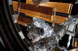 Astronauti Nick Hague a Anne McClain pri práci mimo kozmickej stanice (naozaj sú tam, v strede obrázku – hľadajte nohy). Kredit: NASA.