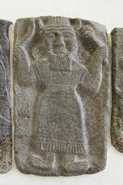 Reliéf boha analogického s Kumarbim, hlavním bohem Hurritů. V rukou drží srp a mužství svého otce. Tell Halaf, 9. století před n. l. Vorderasiatisches Museum Berlin. Kredit: Zde, Wikimedia Commons.