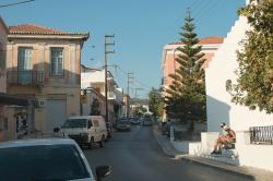 Od zastávky v Chalki. Tahle hlavní silnice pokračuje do Filoti, destilérka je v uličce hned vlevo. Kredit: Zde, Wikimedia Commons. Licence CC 4.0.