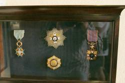 Medaile, které produkt likérky v Chalki obdržel začátkem 20. století. Uprostřed jsou medaile z roku 1904, nahoře z Bordeuax, dole z Marseille. Kredit: Zde, Wikimedia Commons. Licence CC 4.0.