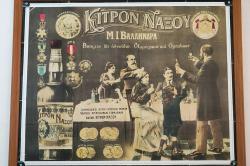 """Osvěta přináší Kitron Naxou do každé lepší rodiny, dítko ovšem vzpíná ručičky marně. Řecký nápis: """"Ústní lékaři (možná spíše zubaři) doporučují pouze neškodný aperitiv a ústní nápoj Kitron Naxou."""" Kredit: Zde, Wikimedia Commons. Licence CC 4.0."""
