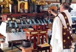 Běžný církevní pohřeb. Pouze máry jsou upravené tak, aby se na ně vešlo nebožtíků devatenáct. Jména pozůstalých, jimž za doby svého života věrně sloužili a kteří obřad zaplatili, jsou uvedena na modrých visačkách. Mši slouží představený kněz Bungen Oi ve starobylém chrámu Kófuku-ji (Isumi, pefektura Chiba). Kredit: Miwa Suzuki, AFP