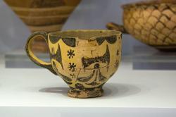 : Hrníček zdobený dvojitými sekerami, z paláce v Archanes na Krétě, 1600-1450 před n. l. Archeologické muzeum v Irakliu (Herakleonu), skříň 42. Kredit: Zde, Wikimedia Commons