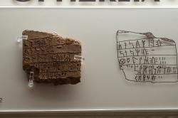 """Fragment tabulky s nápisem v lineárním písmu B: """"Sýpky (nebo Sitopotnia, Paní obilí) a řemeslníci z modrého skla (pracující s modrým sklem?)."""" Z kultovního centra v Mykénách, 1250-1180 před n. l. Archeologické muzeum v Mykénách, MM 2044. Kredit: Zde, Wikimedia Commons. Licence CC 4.0."""