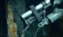 """Rameno manipulátoru dálkově ovládaného robota """"Jason"""" odebírá vzorek tekutiny proudící z hydrotermálního otvoru v hornině.Obsahuje plyny, které jsou kvůli vysokému tlaku na dně oceánu v kapalné formě.Metan i vodík nejsou dílem mikroorganismů v sedimentu. Původ je abiotický a svůj podíl na nich mají  olivíny. Kredit: Chris German / WHOI / NSF, NASA / ROV Jason 2012, Oceanografická instituce Woods Hole."""
