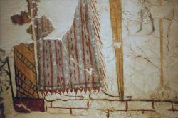 Bosé nohy, sukně a hrot meče bohyně nebo kněžky na levé straně hlavního panelu. Kredit: Zde, Wikimedia Commons. Licence CC 4.0.