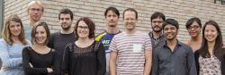 Mladí výzkumníci laboratoře Andrewa Pospisilika (šéf vprvní řadě, vpruhovaném triku) Imunologického a epigenetického ústavu Maxe Plancka ve Freiburgu. Kredit: Max-Planck-Institut für Immunbiologie und Epigenetik