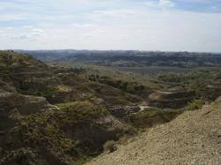 Pohled na sedimenty geologického souvrství Hell Creek na území Státního parku Hell Creek ve východní Montaně. Právě v době ukládání těchto vrstev došlo ve více než 3000 kilometrů vzdálené části proto-Karibiku k osudné srážce. Jak ukazují objevy na několika lokalitách v Montaně a Severní Dakotě, i přes tuto značnou vzdálenost zde měly již první krátkodobé projevy impaktu extrémně devastující účinky. Kredit: Vlastní snímek autora, červenec 2009 (převzetí je možné pouze se souhlasem autora).