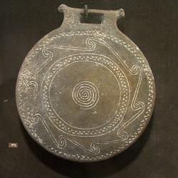 Uprostřed spirála (Slunce?), kolem devítičetná vlnovka. Vryp je zaplněn bílým kaolínem. Průměr 18 cm. Neznámý původ, 2800 - 2300 před n. l. Goulandrisovo Muzeum kykladského umění v Athénách, NG 971. Kredit: Zde, Wikimedia Commons.