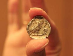 """Stříbrná """"tetradrachma"""". Tato je ze sbírky uchovávané v McMasterském muzeu.Mince se datuje do doby po 449 př.nl a její hodnota byla čtyři drachmy.Na jedné straně je bohyně Athena s přílbou, na straně druhé je sova. Nápis AOE znamená """"z Athén"""".  Kredit: Nasreen Mody, McMaster University,Mississauga, Ontario, Kanada"""