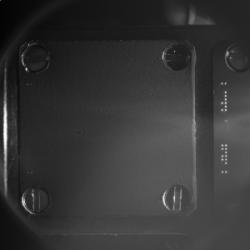 Snímek jedné z cílových plošek detektoru COSIMA. Plátek má rozměry 1×1 cm. Povrch je potažen nanočásticemi zlata a plošku při smínání obrazu před odesláním na Zemi, osvětlí dvě leddiody (jsou vidět vpravo). Destičky pro sběr prachových částic dodala Universität der Bundeswehr. Kredit: ESA