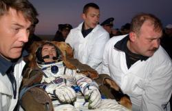"""Jedním z přeborníků na pobyt mimo naši matičku Zemi je ruský kosmonaut Sergej Krikaljov. Nebyl """"doma"""" celkem 803 dní. Rekordu dosáhl postupně v lodích Sojuz, na americkém raketoplánu, na stanicích Mir a ISS.  Na obrázku je po jedné z déle trvajících misí a neschopný pohybu v péči kolegů z pomocných jednotek. (Kredit: NASA)"""