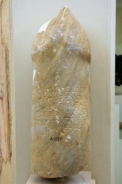 Kamenný fallos v nadživotní velikosti s votivním nápisem, který popisuje okolnosti jeho vztyčení. Archeologické muzeum na Délu. Kredit: Zde, Wikimedia Commons.