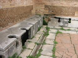 Římské veřejné toalety,Ostia Antica. Kredit: Wikipedia, Veřejná doména.