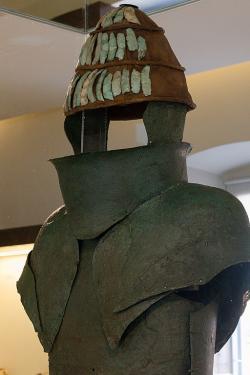 Bronzové brnění a rekonstruovaná přilba z kančích klů s bronzovými lícnicemi. Dendra, konec 15. století před n. l. Archeologické muzeum v Naupliu. Kredit: Zde, Wikimedia Commons. Licence CC 4.0.