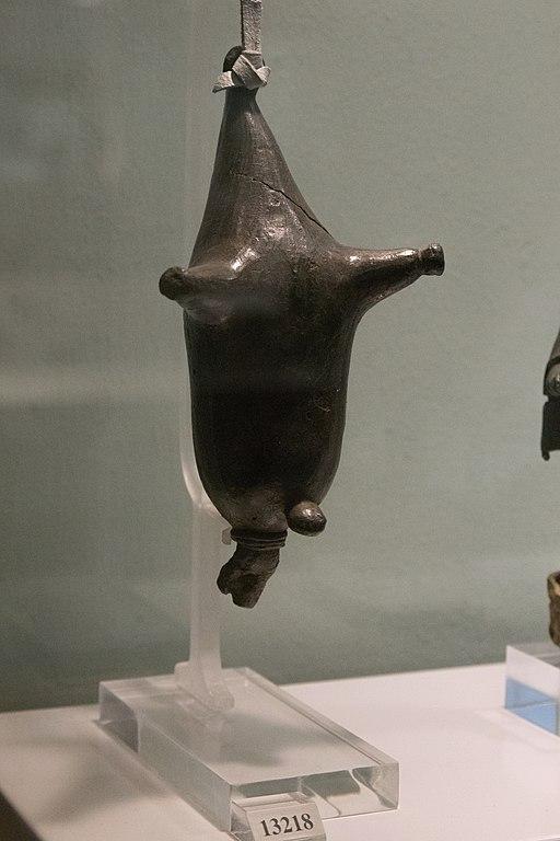 Votivní malý bronzový model koženého měchu na víno (askos) se závěsným kroužkem. Ze svatyně Dia Lykaia na hoře Lykaión. Národní archeologické muzeum v Athénách, č. 13218. Kredit: Zde, Wikimedia Commons