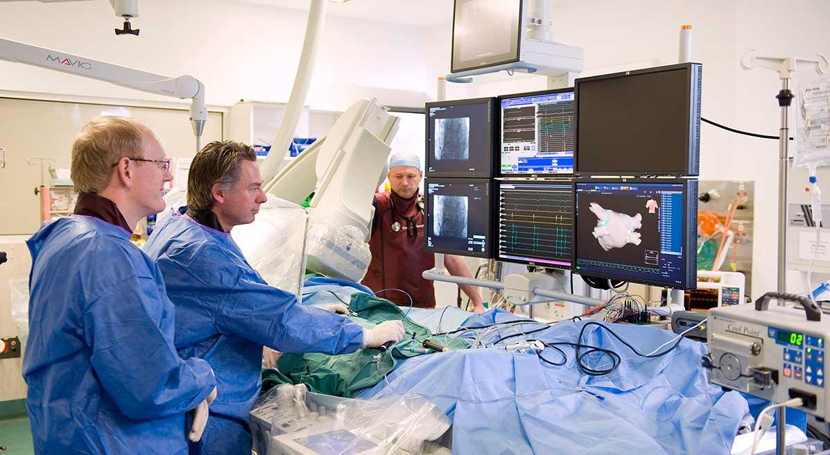 Pracovisko pre rádiofrekvenčnú abláciu v akcii. Ľavá dvojica monitorov poskytuje rentgenový obraz polohy elektród, prostredná sériu EKG kriviek z rôznych miest srdca, vpravo je zobrazený model srdcových predsiení. (Kredit: Melbourne Hea